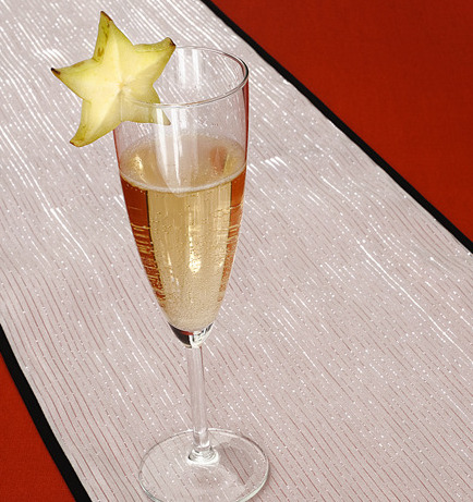 A glass of champagne garnished with a star fruit